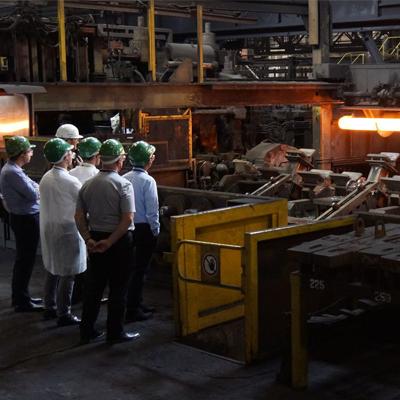 men in front of machine making tubes